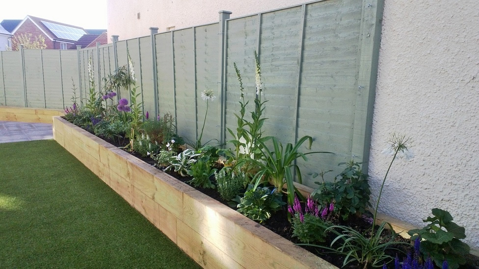 Artificial grass raised beds patio with seating for Grasses planting scheme